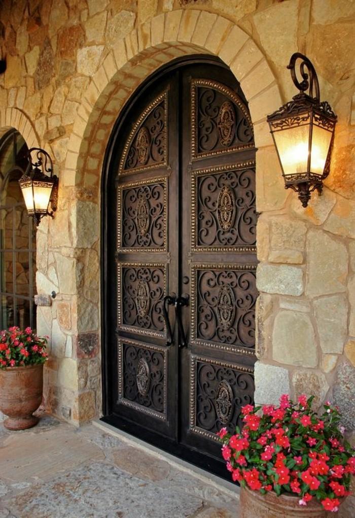 porte-en-fer-forge-facade-en-pierre-maison-en-style-rustique-pots-a-fleur-ceramiques