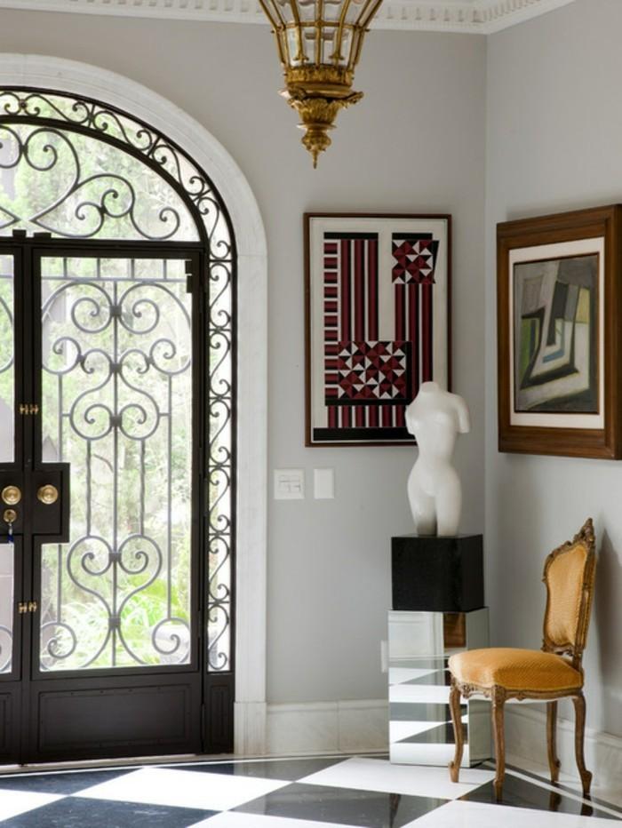 porte-en-fer-forge-lustre-en-or-peinture-art-contemporain-statuette-chaise-en-bois-plafond-en-platre