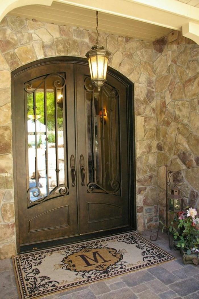 porte-en-fer-forge-paillasson-exterieur-facade-en-pierres-fleurs-arc-en-bois