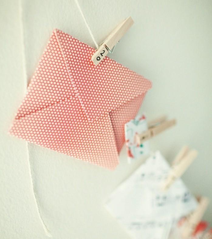 suspendre-les-enveloppes-miniatures-a-des-pinces-a-linge-en-bois-idee-calendrier-de-l-avent-a-fabriquer-soi-meme
