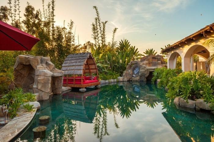 1piscine-avec-cascade-cabane-tropicale-avec-des-coussins-décoratifs