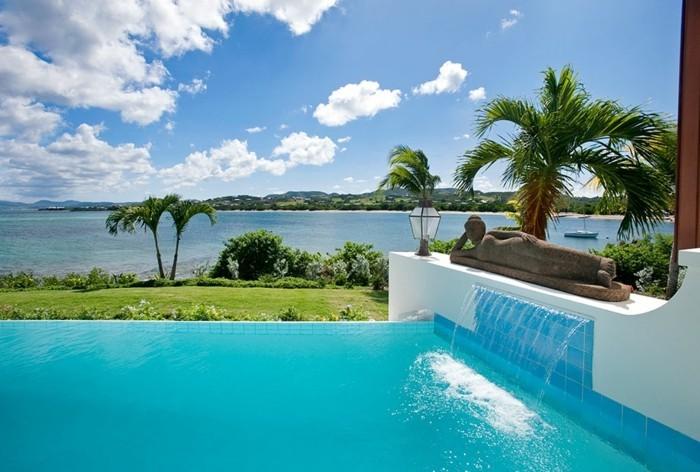 1piscine-avec-cascade-statuette-plantes-tropicales-vue-sur-l'océan