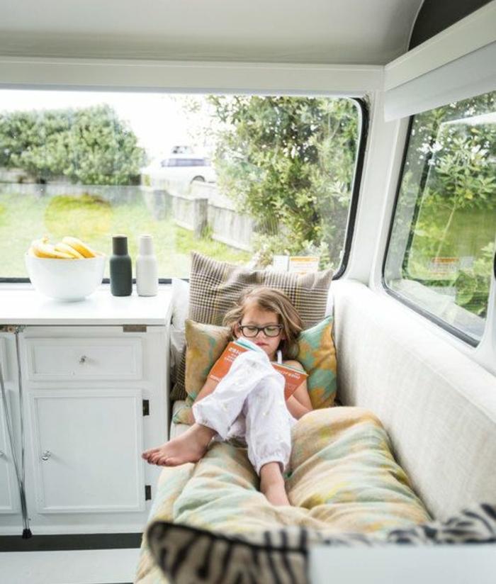 1vivre-en-caravane-enfant-se-reposant-dans-son-lit-confort-et-doux-grandes-fenetres