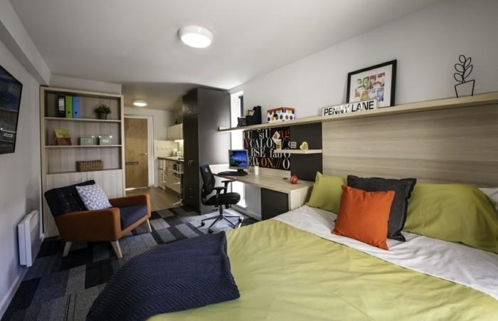 amenagement-petit-espace-grand-lit-couverture-en-vert-coussins-fauteil-confortable-bureau