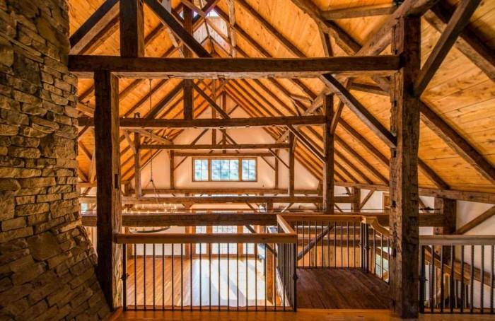 amenager-une-grange-colonnes-en-pierres-garde-corps-en-bois-plafond-avec-poutres-en-bois
