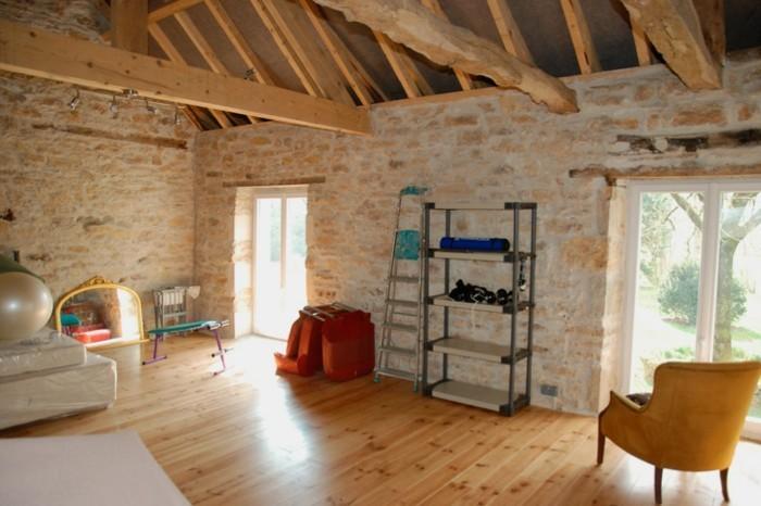 amenager-une-grange-echelle-decorative-etagere-plafond-et-parquet-en-bois-fauteuil-jaune-mur-en-pierre