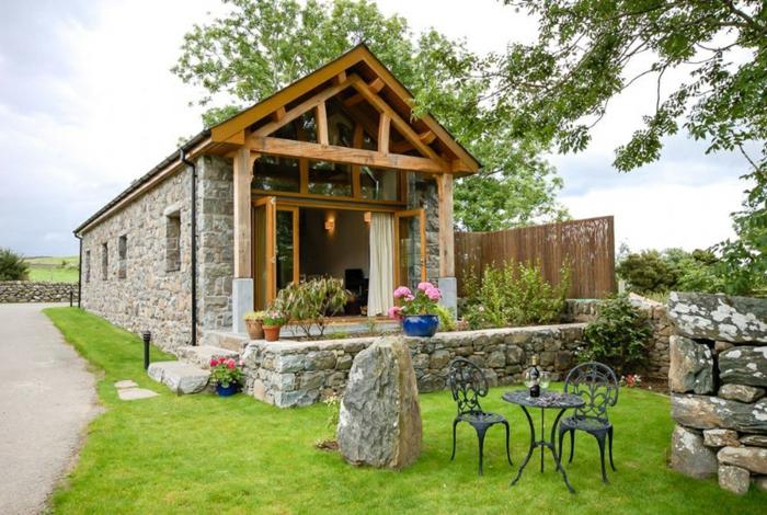 amenager-une-grange-facade-en-pierre-plafond-en-bois-arc-jardin-bien-soine-chaises-en-fer-forge