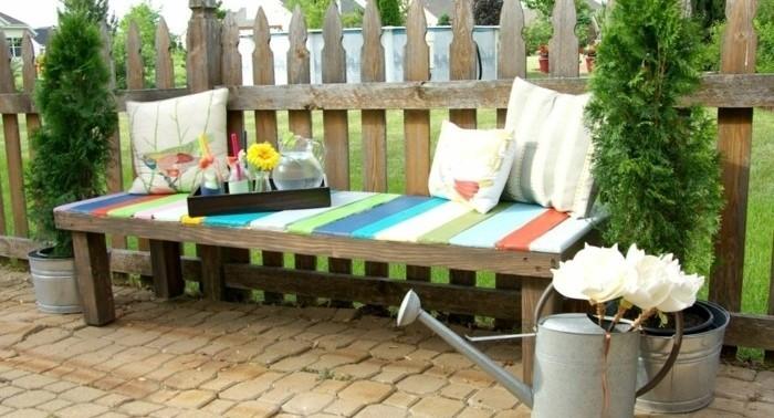banc-en-palette-siege-de-palettes-de-couleurs-diverses-effet-arc-en-ciel-coussins-a-motifs-floraux-banc-posé-pres-d-une-palissade