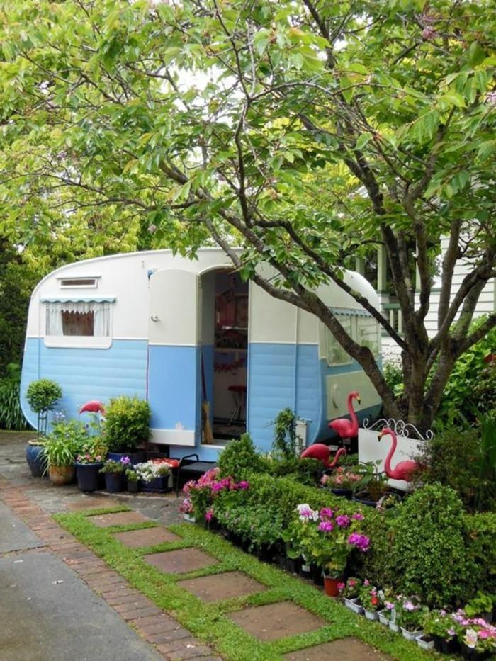 camion-caravane-façade-en-blanc-et-bleu-plantes-vie-en-plein-air