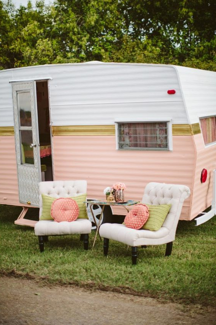camion-caravane-façade-en-blanc-et-rose-couleurs-pastels-fauteuils-pour-un-repos-en-plein-air