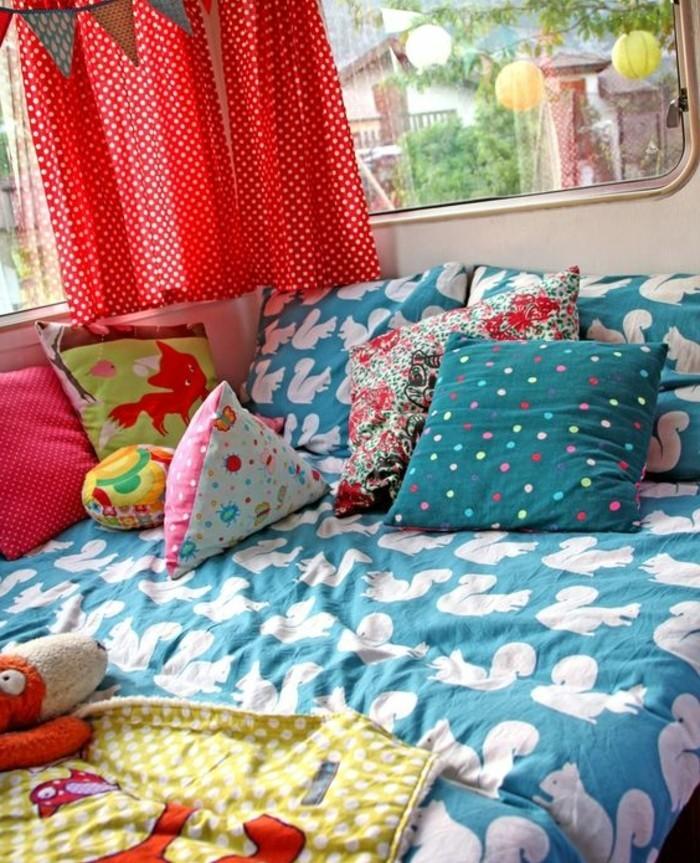 camion-caravane-lit-enfant-couverture-de-lit-bleu-avec-des-coussins-colorés