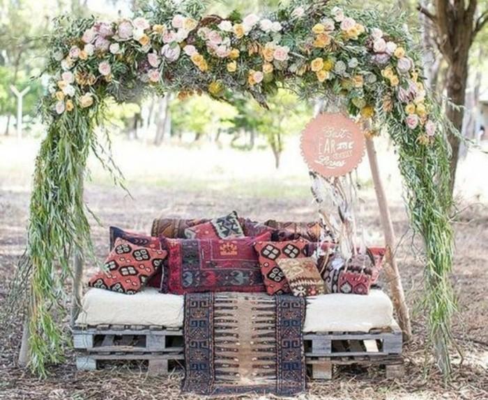 canapé-en-palette-décoré-de-coussins-style-oriental-sous-un-autel-fleuri-decoration-palettes-mariage-boheme-chic