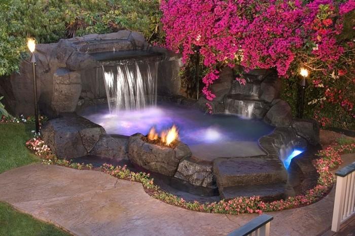 cascade-bassin-avec-des-fleurs-et-plantes-roses-feu-allumé