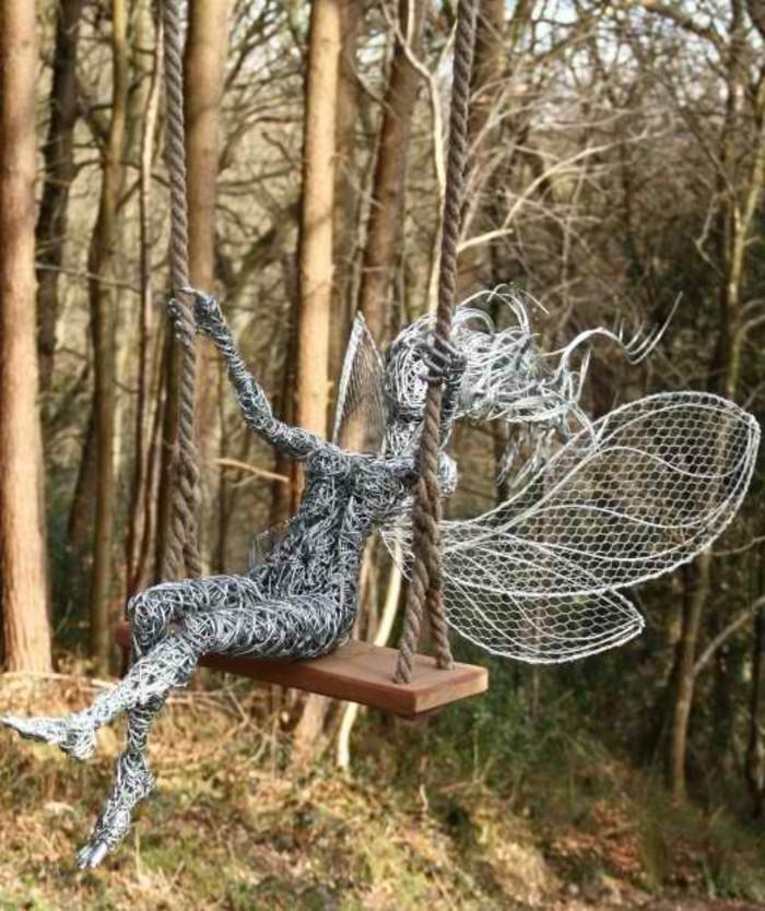 creation-fil-de-fer-figurine-feminine-sur-une-balancoire-dans-la-foret