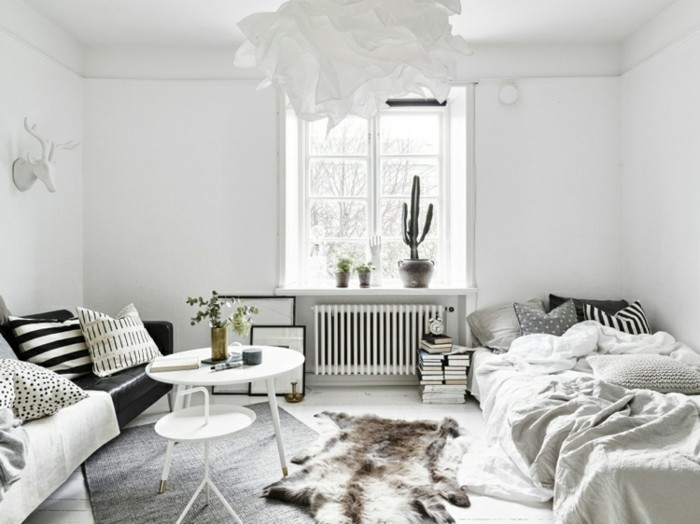 deco-scandinave-lit-bas-canape-noir-coussins-a-motifs-divers-en-gris-blanc-et-noir-quelques-plantes-table-basse-blanche-et-suspension-qui-imite-une-fleur-blanche