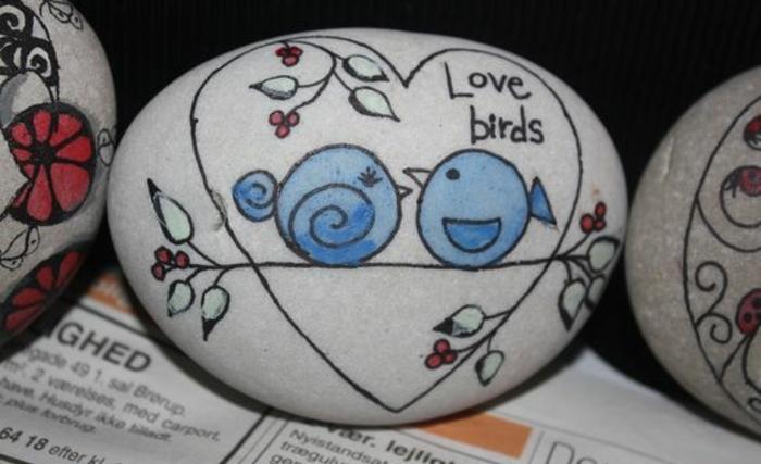 dessin-sur-galet-peinture-acrylique-petits-oiseaux-bleus-et-branches-fleuries-galets-décoratifs