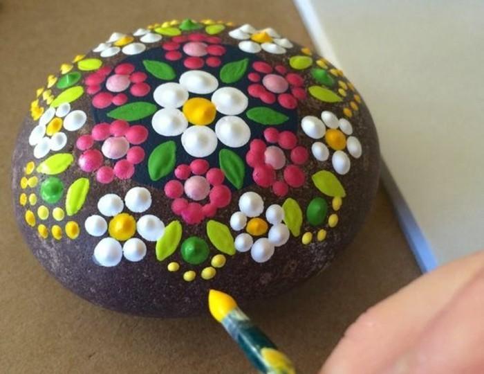 exemple-de-galet-peint-a-motifs-floraux-teintes-claires-nuances-vert-rose-blanc-jaune