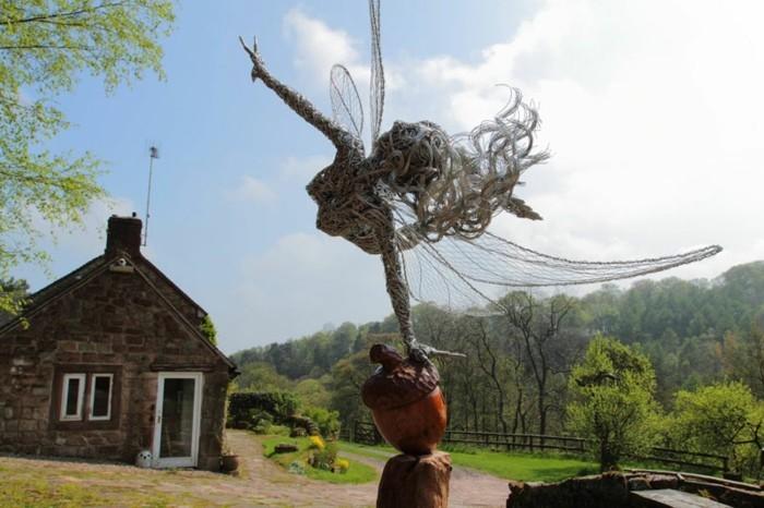 figurine-fil-de-fer-sculpture-de-femme-devant-une-maison-en-briques