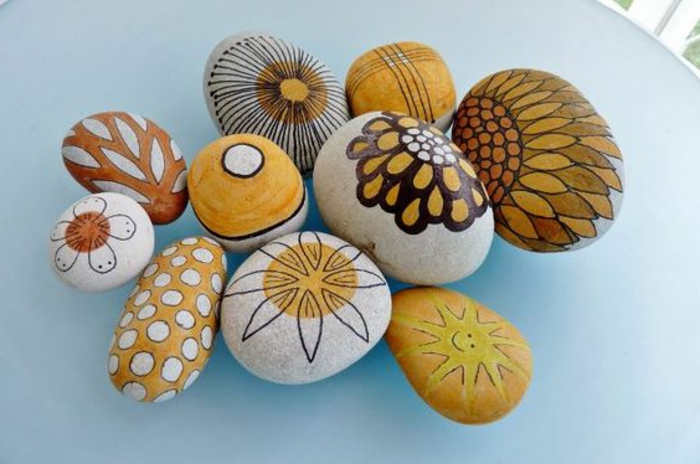 galets-peints-a-la-mains-idee-de-dessin-sur-galets-dans-des-tonalités-jaunes-et-oranges