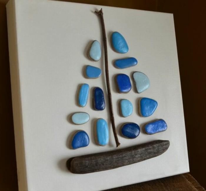 galets-peints-en-bleu-et-de-petits-morceaux-de-bois-arrangés-pour-figurer-un-bateau-idee-d-activité-manuelle-maternelle