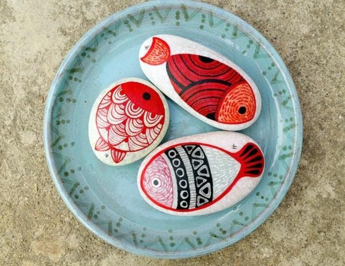 galets-peints-poissons-rouges-dessinés-sur-la-surface-des-galets-idee-d-activité-créative-et-de-déco