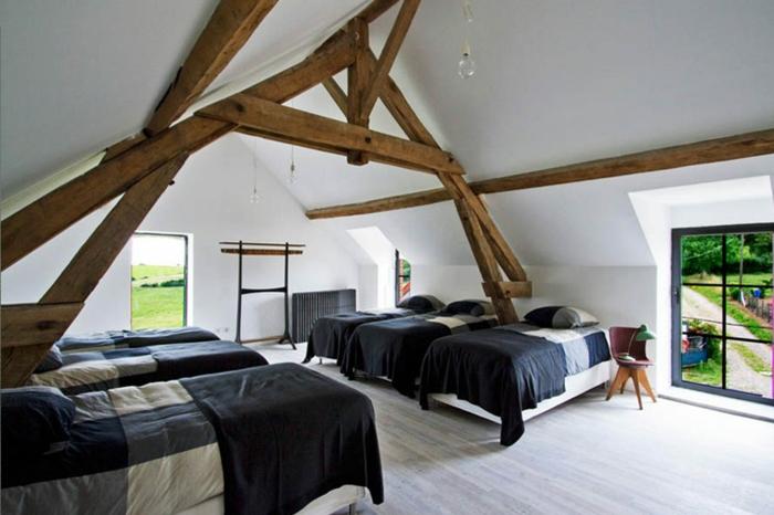 grange-renovee-ambiance-claire-lumire-naturelle-lits-en-couvertures-doux-bleu-fonce-et-gris