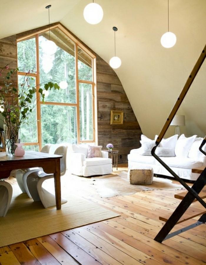 grange-renovee-canape-et-fauteuils-blancs-table-en-bois-branches-poufs-fleurs-vase-boules