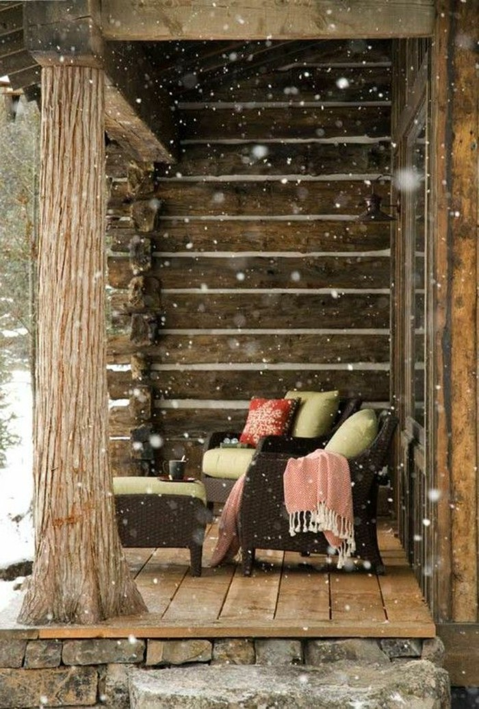 hauteur-neige-cabine-en-bois-salon-de-terrasse-fauteuils-et-table-en-bois-couverture-rose-et-housse-rouge