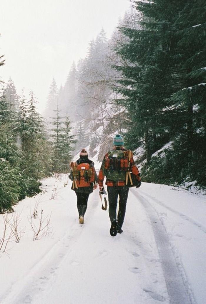 hauteur-neige-couple-avec-des-sacs-à-dos-équipement-bonnets-sentier-dans-la-montagne