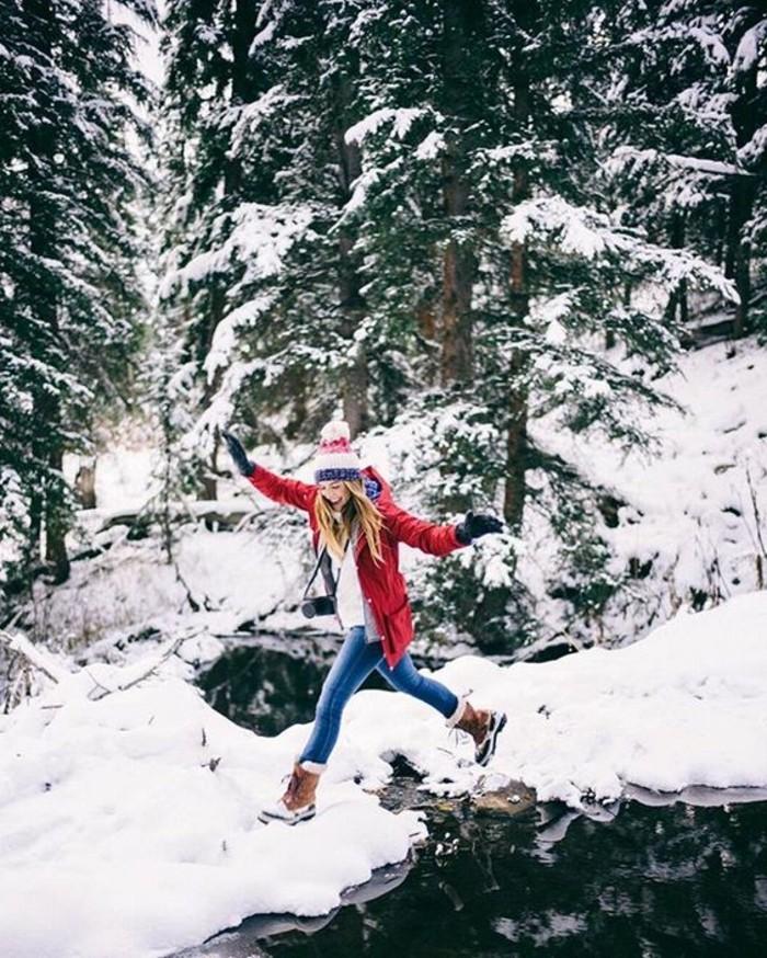 hauteur-neige-fille-veste-rouge-bottes-marron-paire-de-jeans-bonnet-blanc-rouge-et-bleu