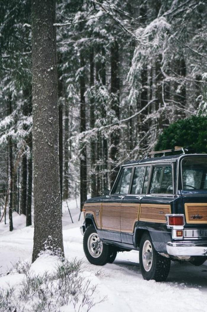hauteur-neige-jeep-avec-un-sapin-de-noel-sur-le-toit-foret-enneigée