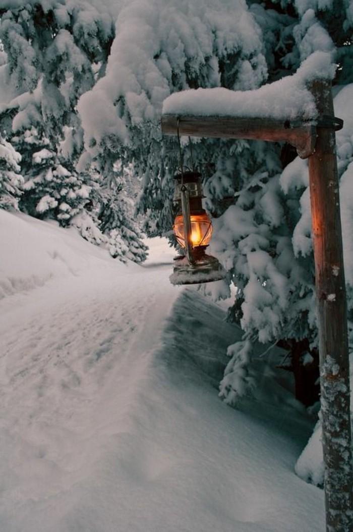 hauteur-neige-lanterne-à-gaz-allumée-sentier-dans-la-montagne-enneigée