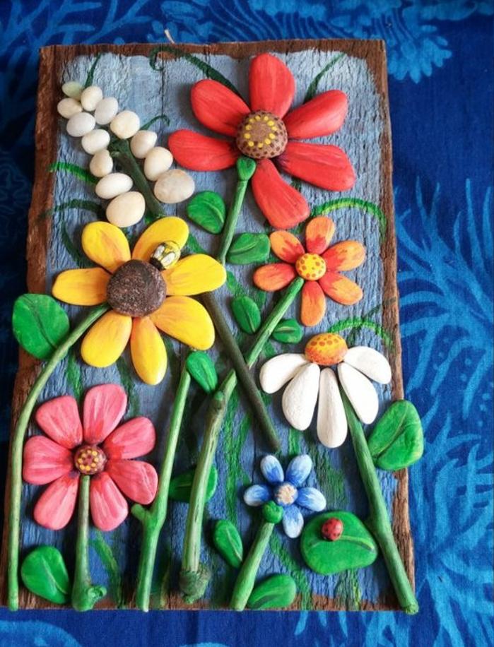 idee-d-activité-créative-galets-décoratis-peintes-en-couleurs-diverses-et-assemblées-pour-constituer-des-fleurs-un-panneau-decoratif-floral-de-galets