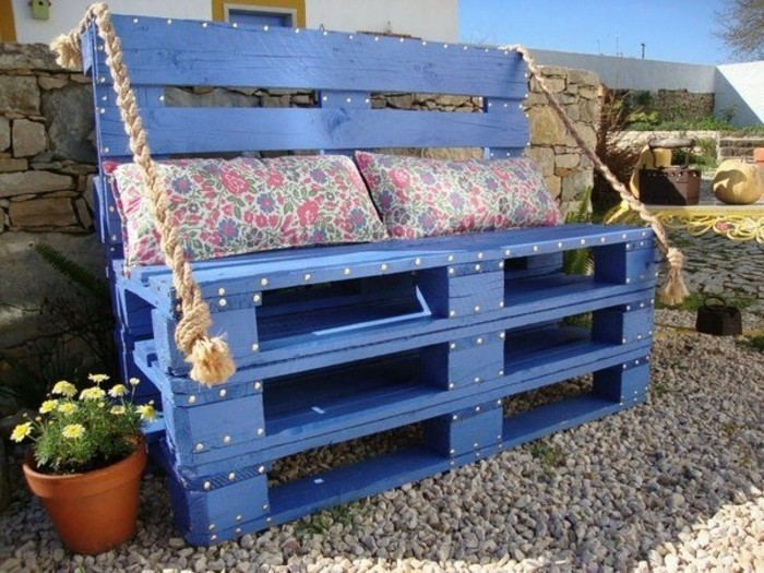idee-de-canapé-en-palette-peint-couleur-violette-posé-sur-du-gravier-dans-un-jardin-coussins-shabby-chic-motifs-floraux