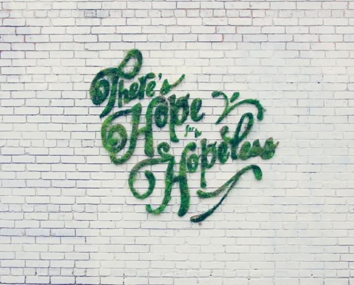 inscription-en-mousse-sur-mur-en-briques-blanches