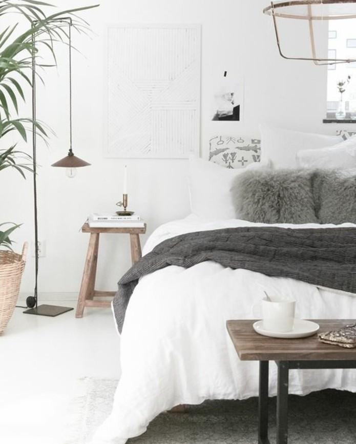 linge-de-maison-blanc-couverture-grise-et-coussins-gris-bout-de-lit-en-bois-a-pieds-metalliques-lampadaire-scandinave-murs-blancs