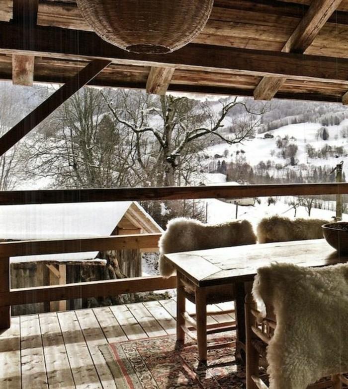 montagne-enneigée-cabine-en-bois-terrasse-donnant-sur-les-montagnes-table-en-bois