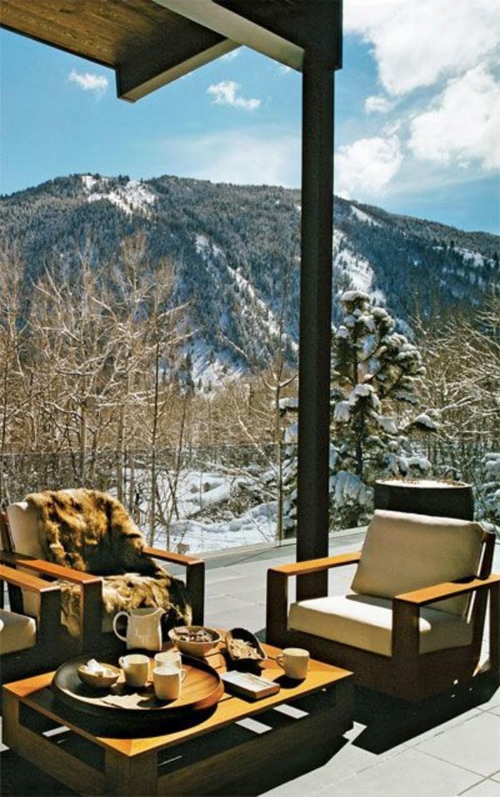 montagne-enneigée-hotel-dans-la-montagne-salon-de-terrasse-fauteils-et-table-en-bois