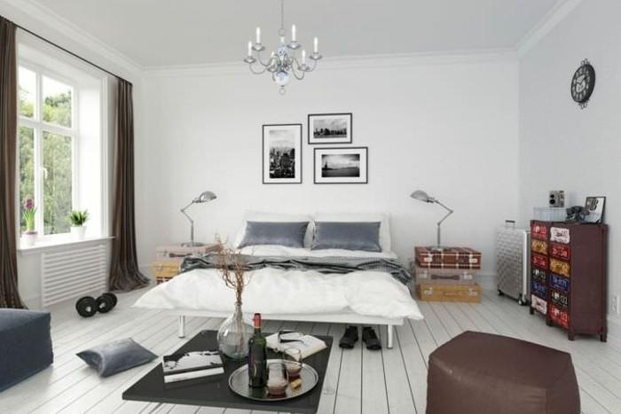 mur-et-sol-en-blanc-lit-a-pieds-hauts-commode-facade-decoree-multicolore-housses-oreillers-grises-malles-decoratifs-enpiles-en-guise-de-table-de-chevet