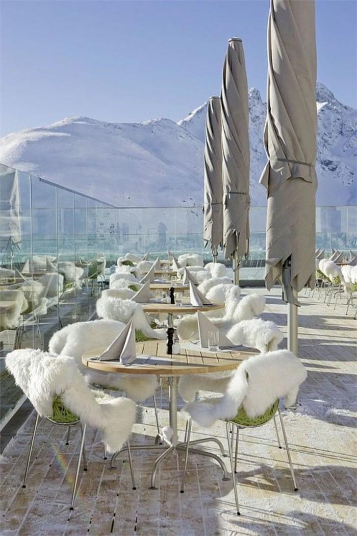 paysage-montagne-neige-terrasse-d'un-hotel-dans-les-montagnes-tables-ronds-couvertures-en-fausses-fourrures