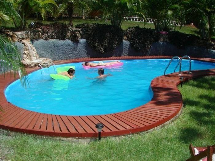 petite-piscine-enterree-forme-de-rein-margelle-en-pierre-gazon