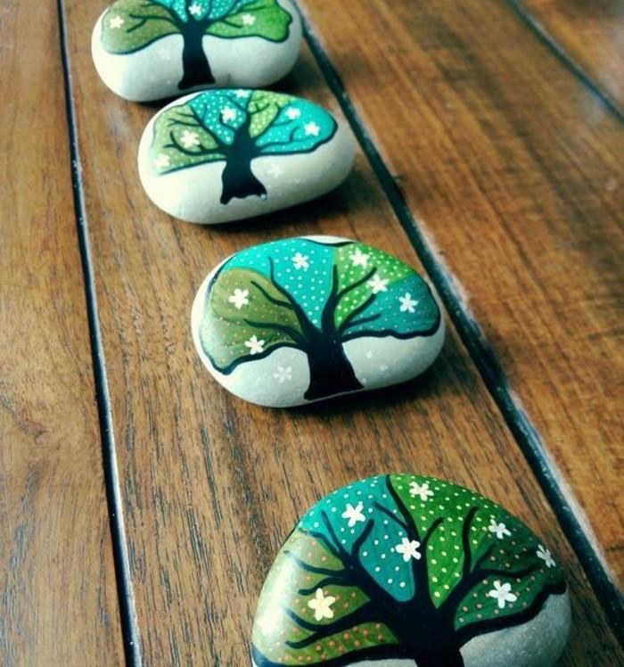 petits-galets-gris-décorés-d-arbres-couronne-d-arbre-verte-parsemée-de-petites-fleurs-blanches