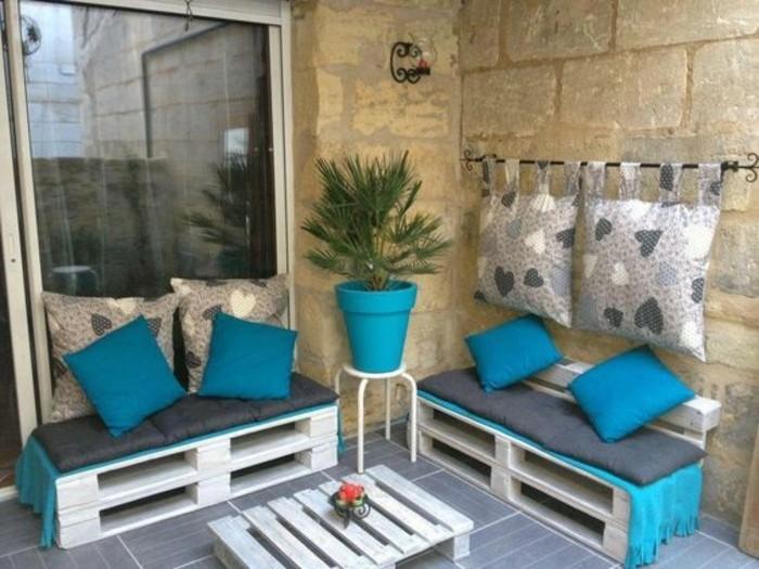 salon-de-jardin-en-palette-table-basse-en-palette-blanchie-petit-canapé-en-palette-peint-en-blanc-coussins-bleus-idee-dec-avec-palettes