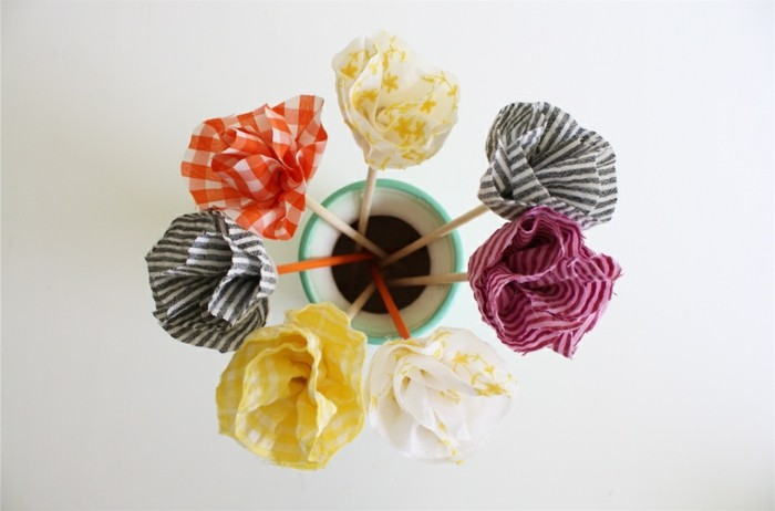 tissu-a-differents-motifs-plié-pour-fabriquer-des-fleurs-idee-comment-faire-des-fleurs-en-tissu-pour-decorer-une-piece