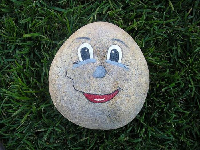 traits-de-visage-de-petit-bonhomme-dessinés-sur-une-pierre-galets-décorés-activité-créative-pour-enfant