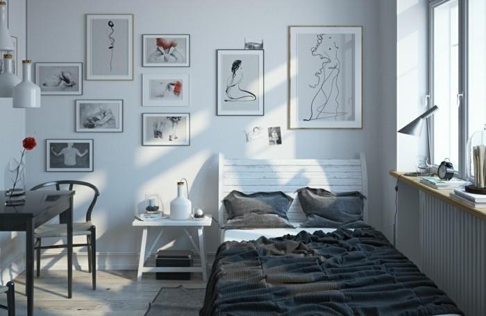 un-lit-minialiste-avec-une-tete-de-lit-en-bois-use-couverture-oreillers-grises-tables-et-chaises-couleur-grise-et-plusieurs-tableaux-graphiques