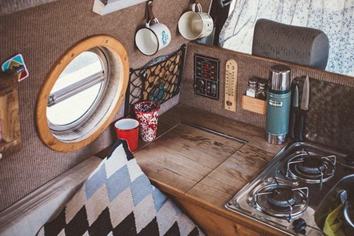 vivre-dans-une-caravane-cuisine-en-taupe-bien-équipée-coussins-décoratifs