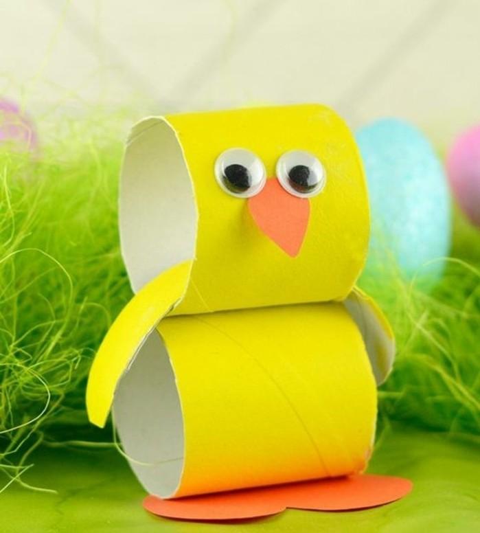 poussin jaune réalisé avec des rouleaux de papier toilette peints en jaune, pieds et bec orange, des yeux mobiles
