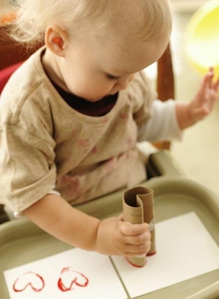 activité créative convenable pour les plus petits, des coeurs empreintes sur du papier à l'aide d'un rouleau de papier toilette