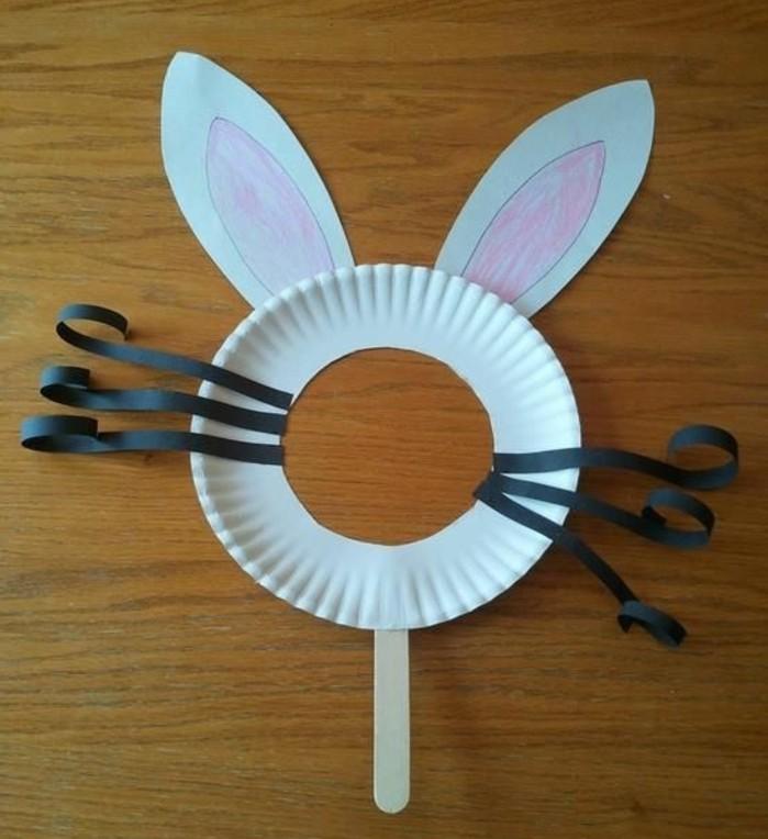 une assiette en papier avec des moustaches noirs en papier, et des oreilles en papier, une masque de paques, activité manuelle maternelle printemps